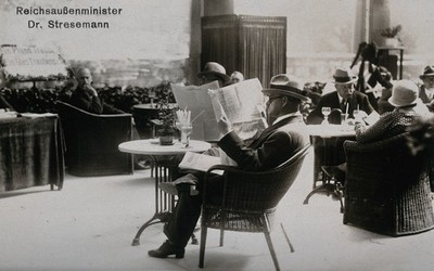 Image from object titled A man reading newspapers on a cafe terrace