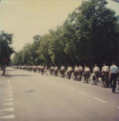 Image from object titled Patiënten van het Sint Elisabeth Verpleeghuis krijgen een uitje naar het Dierenpark Amersfoort. Militairen duwen de rolstoelen met de patiënten in een lange optocht over de           Barchman...