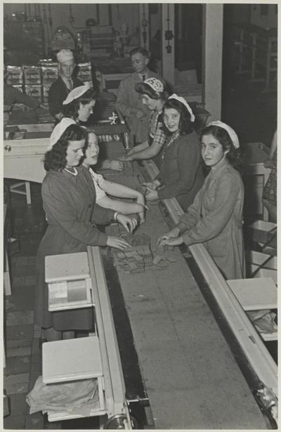 Image from object titled Meursing's Machinale Fabrieken van Gebak aan het Smallepad: iin de nieuwe fabriek worden aan de lopende band wafels ingepakt. Links vooraan vermoedelijk een meisje           Hagenbeuk.