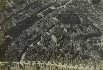 Luchtfoto van Leiden met linksboven de Pieterskerk op het Pieterskerkhof en in het midden de Hooglandse Kerk aan de Nieuwstraat.Rechts boven de Hooglandse Kerk in           de bosschages De Burcht.