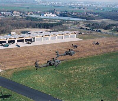 Twee Apaches vliegen over het vliegveld Gilze-Rijen. Twee andere Apaches staan op het platform.