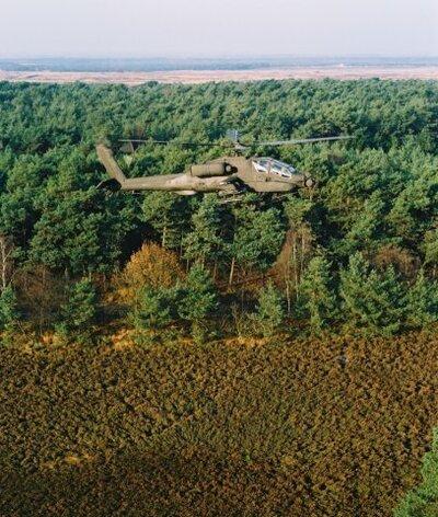 Een Apache vliegt boven de heide.