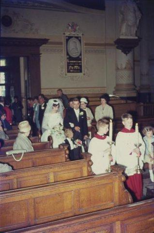 In de r.k. Johannes de Doperkerk (Havenkerk) aan de Lange Haven 72 wordt op 28 mei 1964 het kerkelijk huwelijk voltrokken tussen M.A.A.van der Moezel en C.C. Ruts. Hier de           plechtige binnenkomst.Bruidsjonker is...