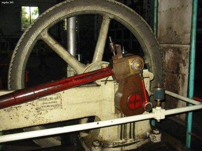 Een eencilinder horizontale stoommachine, gefabriceerd door Machinefabriek N.V. Ingelse en co aan de Nieuwe Haven, draaiend in een suikerfabriek in Watullis op Java. Te zien           is het aandrijfwiel en de naamplaat...