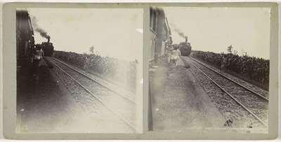 Vrouwen lopen met manden tussen twee spoorlijnen