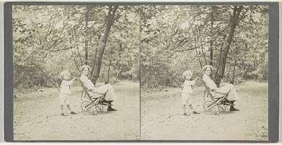 Jongen duwt een kinderwagen waar een vrouw in zit