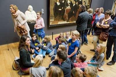 Image from object titled Medewerkster van de Afdeling Publiek & Educatie met een groep kinderen op zaal; Rijen bezoekers en drukte in de herfstvakantie