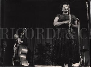 Ella Fitzgerald ritratta a figura intera, frontalmente, durante un concerto. Ritratto femminile