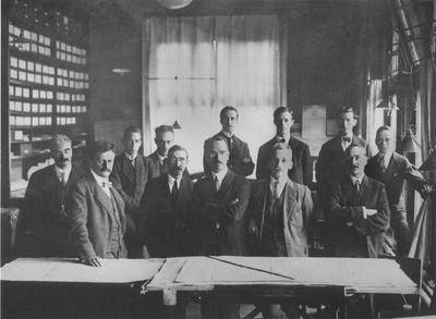 Groepsfoto op kantoor Heerlen. De foto is genomen in 1918. V.l.n.r. eerste rij prof. dr. ir. F.K.Th. van Iterson, hoofdingenieur R. van Vloten, Kroeze, ir. E.C. von Pritzelwitz van der Horst, ir. J.F. Valstar en Greven. Achterste rij ir. N.P. Pel, ir. Holger, van de Graaf, C.J.F. Bloemink, Schoonbrood en Wachelder