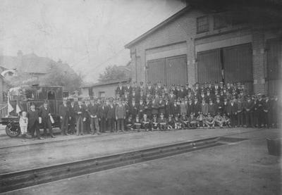 Foto van het personeel spporwegbedrijf van de Staatsmijnen in Limburg. Opname  gemaakt ter gelegenheid van het behalen van de eerste prijs in een optocht ter gelegenheid van het 25-jarig bestaan van de Staatsmijnen in 1927. Links de opgetuigde locomotief.