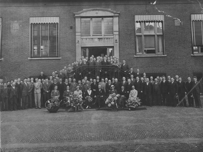 Groepsfoto van beambtenpersoneel voor het gebouw van het laboratorium cokesfabriek Emma te Treebeek. De foto werd genomen bij gelegenheid van de ontvangen koninklijke onderscheiding van hoofdbedrijfsingenieur ir. D.P. (Daan) Ross van Lennep. Hij werd toen benoemd tot officier in de Orde van Oranje-Nassau. In het midden de onderscheiden Ross van Lennep met links zijn echtgenote. Zittend links op de eerste rij is ir. P.C. (Kees) Wichers van het SBB te zien. Achter Wichers staan J.S.A.J.M. van Aken (licht costuum) en rechts naast Van Aken D.W. van Krevelen.