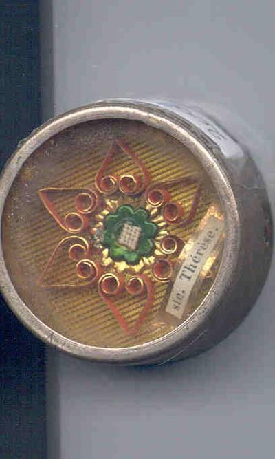 Anoniem, reliquarium met lakstempelafdruk met bloemenmotief waaronder de tektst Ste. Thérèse, s.d., metaal, zegellak, papier, glas.