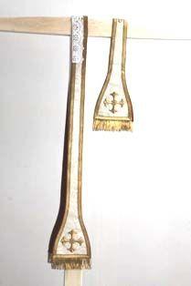 1 stola in witte damast omzoomd met goud galon, waarin een blokjesmotief, en centraal een kruis.