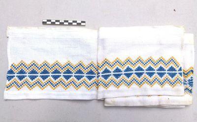 1 communiekleed of afboording in katoen met geel en blauwe kruisjessteek: