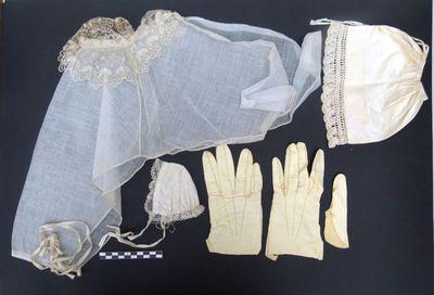1 ronde kraag, 1 paar leren handschoenen en 2 mutsjes - beeldkleding in gele zijde en witte kant