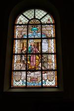 Glas-in-loodraam 'Foltering van de heilige Apollonia op de brandstapel'.