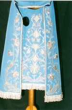 Onze-Lieve-Vrouw met stola, kleed kindje met kraag en strik
