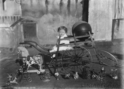 Retrato: nena sentada nun carriño con xoguetes no chan