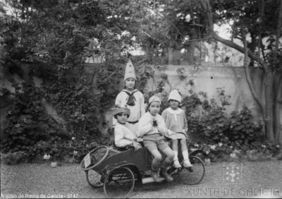 Retrato: catro nenos nun coche de xoguete