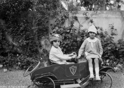 Retrato: dúas nenas nun coche de xoguete