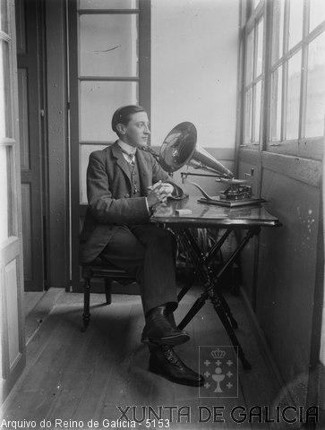 Retrato: mozo sentado escoitando o gramófono