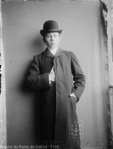 Retrato: rapaz de pé con abrigo e sombreiro
