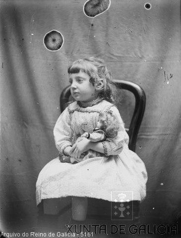 Retrato: nena sentada cunha boneca no colo