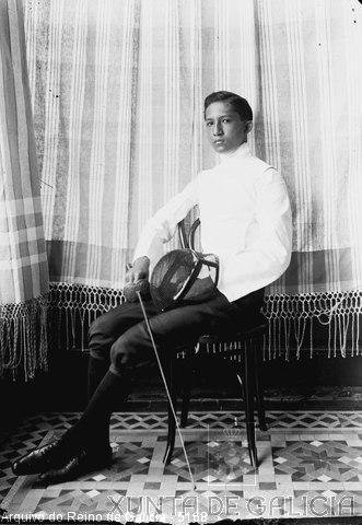 Retrato: rapaz sentado con traxe de esgrima