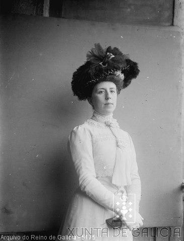 Retrato: muller vestida de branco con sombreiro e carteira