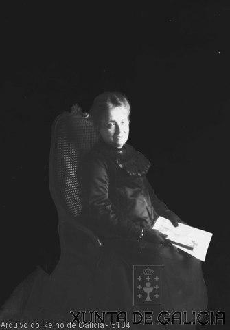 Retrato: muller sentada en mecedora con fotos nas mans