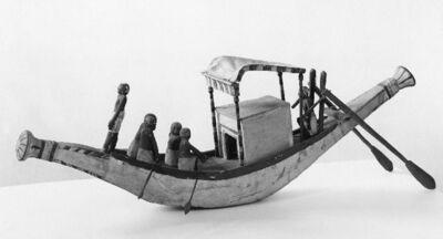 Model van een boot met cabine en baldakijn en zes figuurtjes