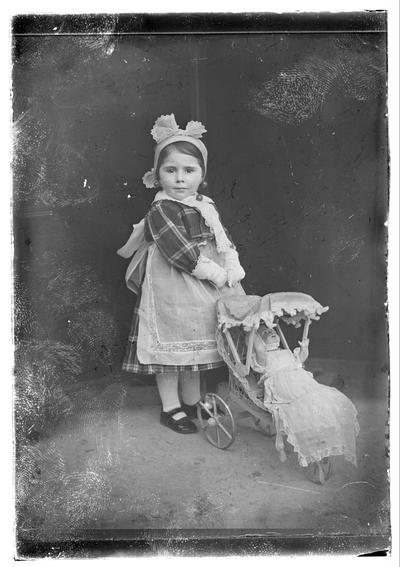 Retrato de niña con carrito de muñecas