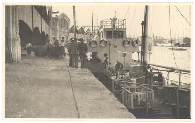 [Barco atracado en el puerto con el depósito de mercancias al fondo] [Material gráfico]: [València].