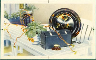 Interiörbild av bord med blomma, fat, kopp och brödrost