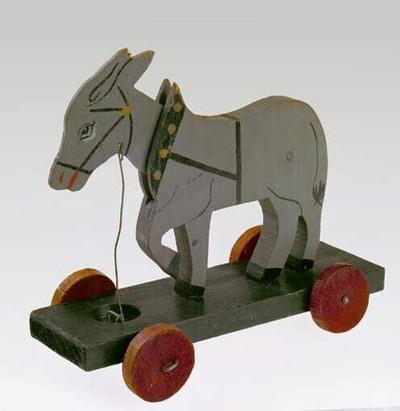 Houten ezel op wielen voorzien van een koordje. De ezel gesneden uit ongeveer één cm. dik hout en is grijs geverfd. Zijn kop kan scharnieren. Hij staat op een donker plankje voorzien van vier rode houten wielen. In dit plankje zit aan de voorzijde een rond gat met een verbinding naar de vooras zodat tijdens het rijden de kop gaat knikken.