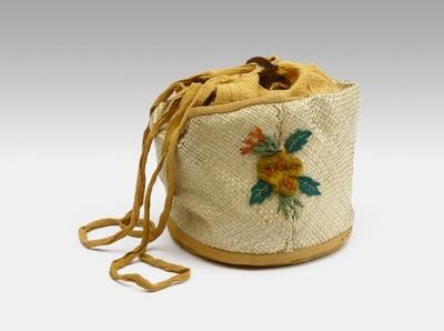 Een ronde van tiker (?) gevlochten tas, van binnen gevoerd met oranje stof. De voering steekt boven het gevlochten deel uit en eindigt in een rijgsluiting. Aan beide zijden van de tas zijn bloemen geborduurd.