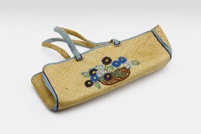 Een langwerpige tas van tikar met bloemen erop geborduurd en afgebiesd met een katoenen strook.