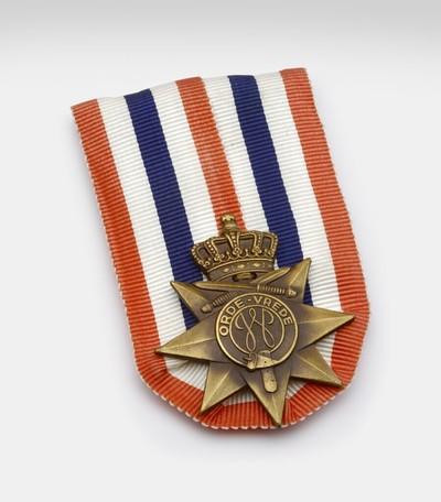 Zevenpuntige ster op rood wit blauw lint. Op de plaats van de denkbeeldige achtste punt bevindt zich een kroon met daaronder twee gekruiste zwaarden. In het midden een medaillon met in een cirkel de letter W en erboven de woorden 'Orde-Vrede'.# Op de achterkant de naam van de maker: Koninklijke Begeer te Voorschoten. # Ingesteld bij Koninklijk Besluit van 2 december 1947 als beloning voor KNIL-soldaten die in de periode 1945-1949 voor ten minste drie maanden in actieve dienst in Nederlands-Indië waren geweest.