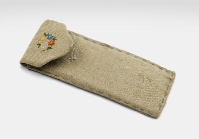 Een stoffen pennenetui versterkt van binnen met tikar. Op het klepje dat de etui afsluit is een kransje met bloemen geborduurd.