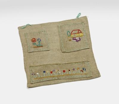 Een doek met vakjes en lussen aan de bovenkant om aan een wand te hangen. Op het doek zijn drie lappen vastgenaaid. Op deze lappen zijn bloemen en een huisje geborduurd.