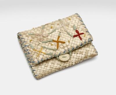 Een met geometrische motieven geborduurde portemonnee. De portemonnee is van gevlochten tikar en de klep wordt afgesloten met een knoop.