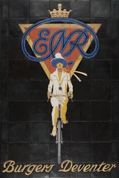 Zwart tableau met opschrift Burgers Deventer met in verschillende kleuren dame op fiets, daarboven blauwe sierletters ENR, Eerste Nederlandse Rijwielfabriek en kroon (vanaf 1869-)
