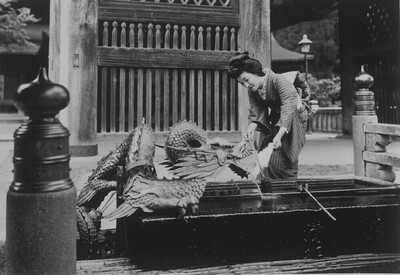 A Japanese woman washing things in a dragon fountain in the Kiyomizu Dera temple in Kyoto, Japan.