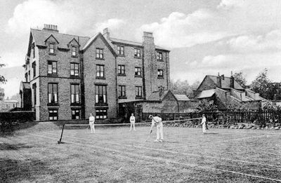 A Fives court at Queen Elizabeth Grammar School with a boys boarding house behind.