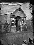 man, child and woman standing outside a shop]