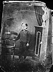 young boy standing next to a chair]