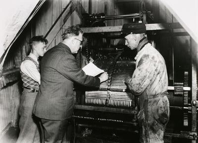 In het midden staat beiaardier Toon van Balkom tijdens het zetten van een nieuwe melodie op de trommel van het carillon