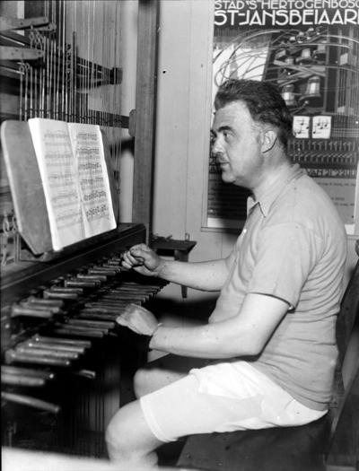 De stadsbeiaardier Toon van Balkom aan het klavier van de beiaard van Sint Jan. Volgens de ideeën van die tijd was hij wegens de heersende hitte