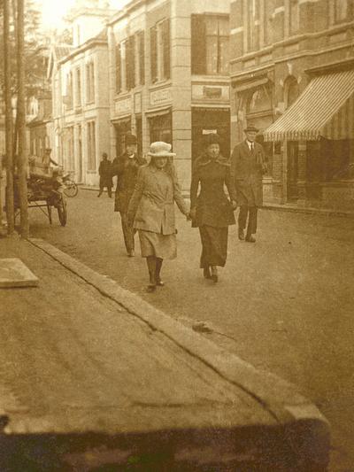 Een winkelende prinses Juliana in gezelschap van een hofdame en achter haar een rechercheur.