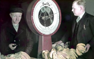 Dia gemaakt door Jan H. Stokking (1916o1975) tijdens de landelijke FoUGAocampagne die de grote veranderingen in het tuinbouwbedrijf en in de handel in groente en fruit onder de aandacht moest brengen. Twee groenteo en fruithandelaren met een weegschaal en trossen bananen